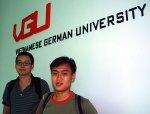 Long und Kai vor dem Schriftzug der Universität.